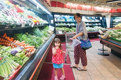 A girl and her mother shop in the fresh produce section of H Mart