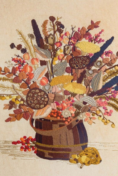 A vintage floral needlecraft, made by Danny Child's great-grandmother, hangs in the couple's home kitchen.