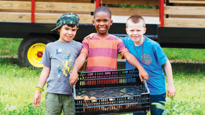 Adrian Lopez, 7, Ethan Davis, 7, and Anthony Salkauski, 8, carry freshly harvested potatoes at Gravity Hill Farm.